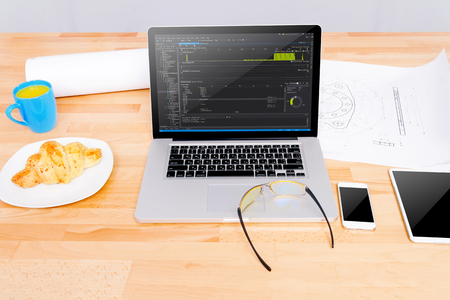 Software engineers workplace with notebook, mockup tablet, glasses, sketching, mockup smartphone, blue cup, croissant. Note: Code was got from github with free license for commercial use (MIT) Stock Photo