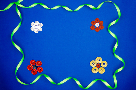 hard: Flowers made of colorful buttons surrounded by a green ribbon isolated on blue background Stock Photo