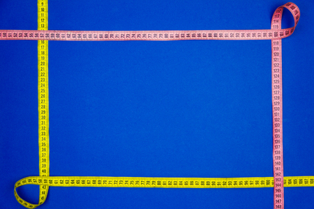 Two measuring tapes isolated on blue background