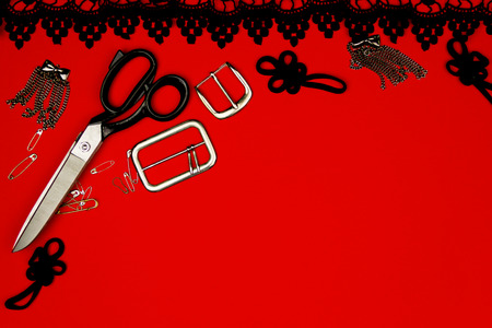 needle laces: Sewing kit isolated on red background: scissors, pins, accessories,  metal buckles, black frill