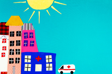 Fabric town. Houses, the sun and ambulance made of colorful pieces of fabric isolated on blue background.