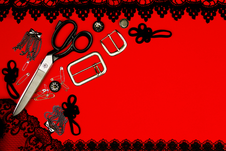 needle laces: Sewing kit isolated on red background: scissors, pins, accessories, buttons, metal buckles, black lace