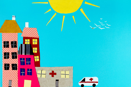 Fabric town. Houses, trees and the sun and ambulance made of colorful pieces of fabric isolated on blue background. Stock Photo