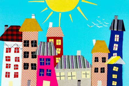 Fabric town. Huizen, de zon gemaakt van kleurrijke stukjes stof geïsoleerd op blauwe achtergrond.