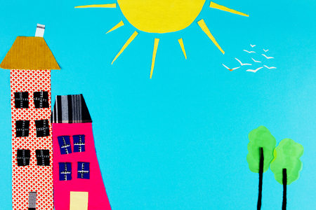Fabric town. Houses, trees and the sun made of colorful pieces of fabric isolated on blue background.