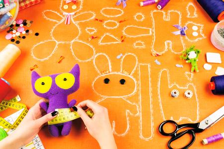 Lieu de travail d'un tailleur: tissu, bobines, ruban à mesurer, boutons, aiguilles, arcs, jouets et dessins. Fille de mesure pourpre jouet avec le ruban à mesurer