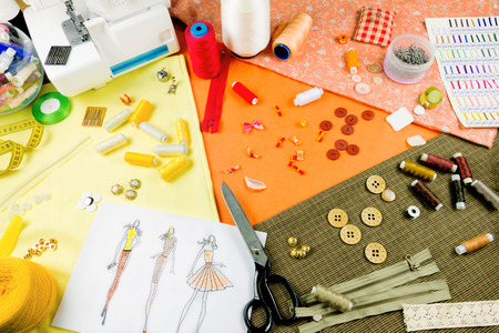drawing pin: Workplace of a dressmaker: scissors, buttons, spools, measuring tape, sketches, fabric, needles, sewing machine and other tools. Stock Photo