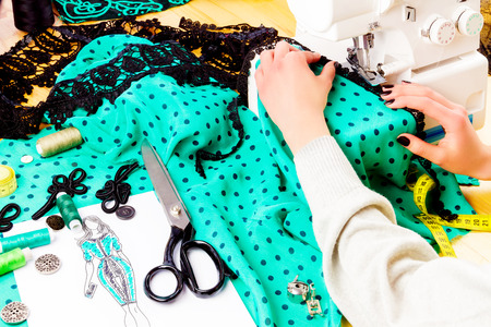 Workplace of a dressmaker: buttons, spools, scissors, sketch, buckle, fabric, lace and beads. Girl sewing dress with the help of sewing machine