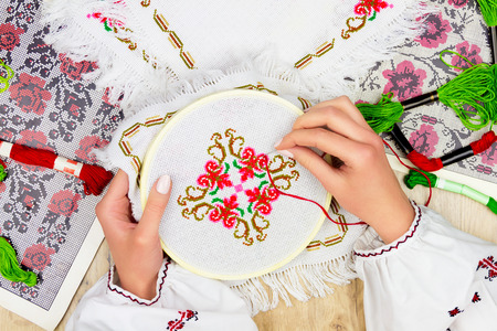 Hands of girl  woman  female in ukrainian traditional shirt sewing embroidery pattern in embroidery frame. Embroidery schemes and colorful threads on background.