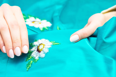 punto de cruz: Hands of girl  woman  female sewing colorful flower ornament by beads on blue shirt  dress. Embroidery concept