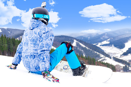 knee boots: BUKOVEL, UKRAINE - MARCH 12, 2017 Man sitting on the top of the alps mountain  wearing a snowboard