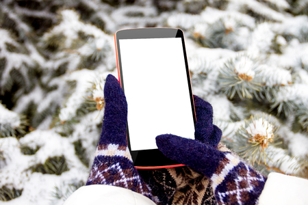 Female  woman  girl hand in mittens with mockup phone  smartphone in winter on fir tree background