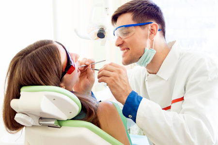 Smiling young man male dentist in medical glasses and mask treatments teeth of woman female patient in red uv glasses by equipment tool implanting medical sealants