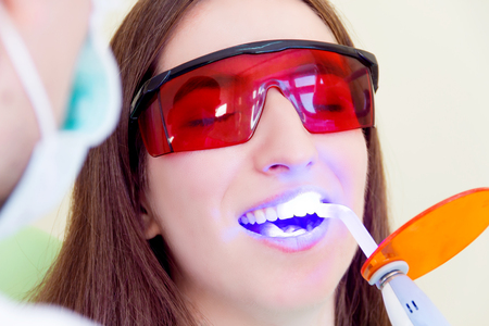 Young man male dentist in medical glasses and mask treatments teeth of woman female patient in red uv glasses by uv equipment tool implanting medical sealants