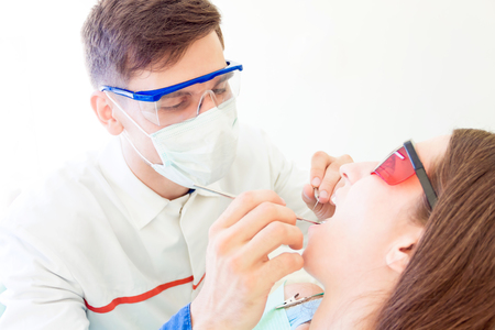 Young man male dentist in medical glasses and mask treatments teeth of woman female patient in red uv glasses by equipment tool implanting medical sealants