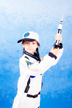 Young child girl female playing in astronaut with rocket toy in white astronaut costume and dreaming about flying into cosmos on blue background Stock Photo