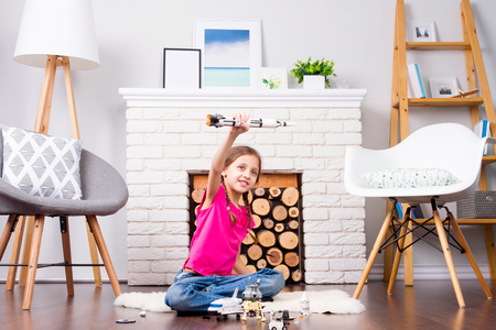 Young child girl female playing with cosmos's toys constructor: rocket, shuttle, rover, satellite and astronaut doll in comfortable interior at home on wooden floor