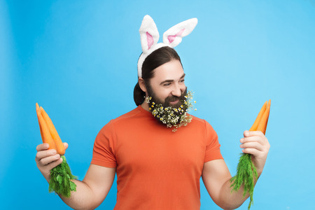 Nice kind muscle man male with spring's flower's beard, white ears of rabbit, carrots in orange t-shirt isolated on blue background