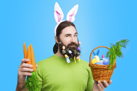 Happy Easter concept. Nice kind muscle man male with beard, white ears of rabbit, carrots and basket with colorful easter eggs and green in green t-shirt isolated on blue background