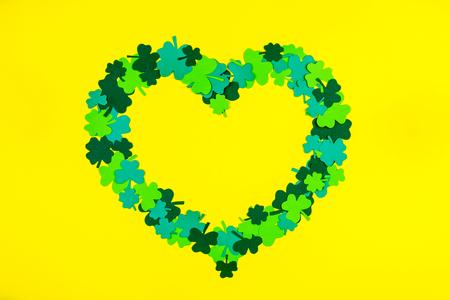 Saint Patricks Day. Heart shape of green three petal clovers lying on yellow background Stock Photo