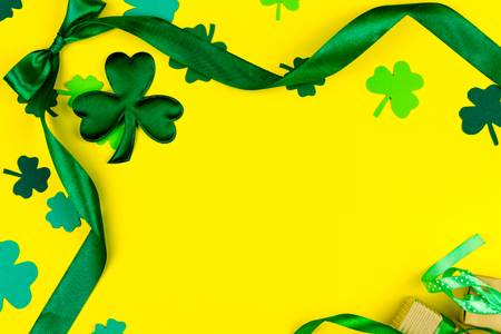 Saint Patrick's Day. Green design curved tape, green three petal clovers and gift's box on yellow background Stockfoto