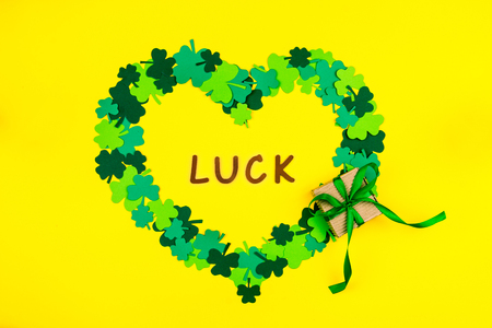 Saint Patricks Day. Wooden letters luck lying on yellow background in heart shape of green three petal clovers with gift box  Stock Photo