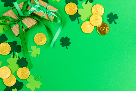 Saint Patrick's Day. Green three petal clovers and gold leprechaun  coins on green background