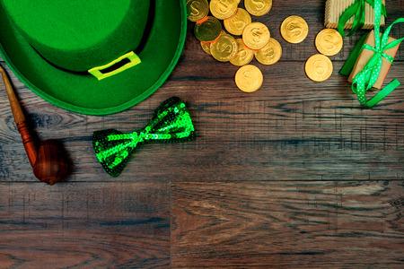 Dzień Świętego Patryka. Zielony kapelusz krasnoludka, zielona muszka, fajka i złote monety na podłoże drewniane