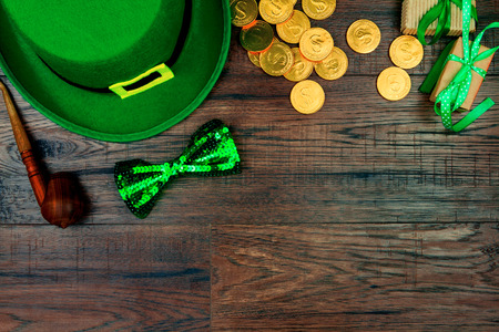 Saint Patricks Day. Green hat of leprechaun, green bow tie, smoking pipe and gold coins on wooden background