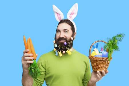 Nice kind muscle man male with beard, white ears of rabbit, carrots and basket with colorful easter eggs and green in green t-shirt isolated on blue background 写真素材