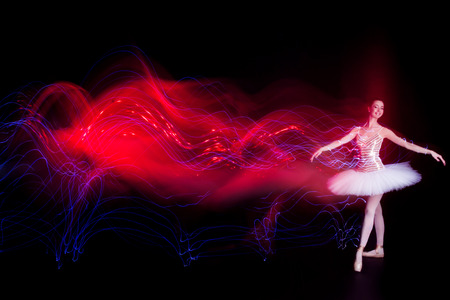 Young female  woman  girl ballerina in a white pack  tutu solo dancing and leaves red light leak trail of silhouette in black scene with reflecting floor and dark background Stock Photo