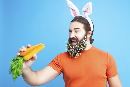 Happy Easter concept. Nice kind muscle man male with springs flowers beard, white ears of rabbit, carrots in orange t-shirt isolated on blue background