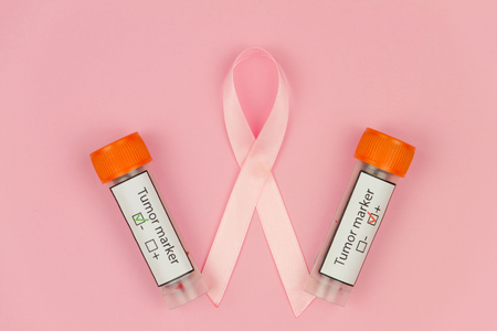 Pink tape as symbol of womens illness mammary cancer with blood test tubes on pink background
