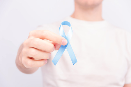 Oncological disease concept. Man in white t-shirt holding light blue ribbon as a symbol of prostate cancer.  Stock Photo