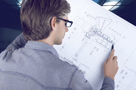 Mechanic engineer workplace. Man / male engineer wearing shirt and glasses looking at  mechanic sketches and analyzing data.