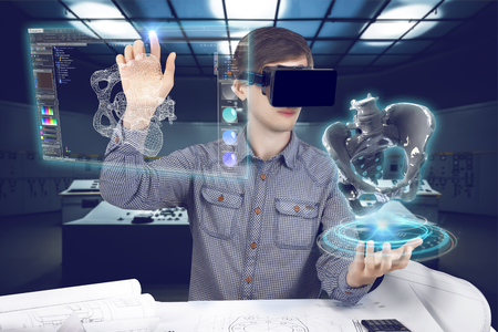 Futuristic medical scientist workplace. Male / man wearing shirt and vr glasses holding holographic prosthesis of coxal and touches virtual screen making medical analysis on futuristic plant background with control panels. Banque d'images