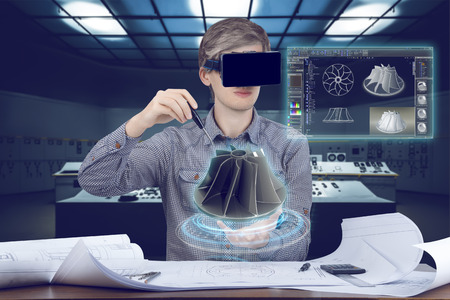 Futuristic cad engineer's workplace. Male / man wearing shirt and vr glasses touches with screwdriver 3d model of turbine and looking at virtual screen analyzing 3 data for mechanic industry on futuristic plant background with control panels.