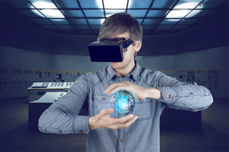 Virtual reality in engineering concept. Male  man wearing shirt and vr glasses holding virtual power sphere in his hands on futuristic plant background with control panels.