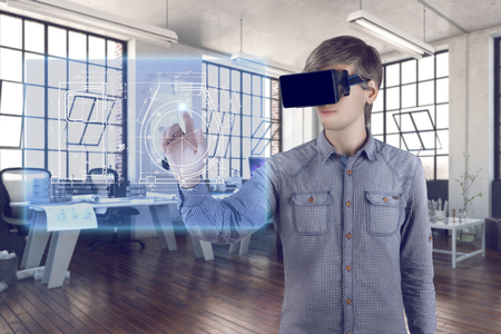 Futuristic engineer workplace. Male  man wearing shirt and vr glasses touches with his hand virtual screen with graphics and sketches of turbine and analyzes 3d data for mechanic industry in the office