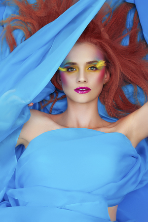 Pretty girl with ginger hair and bright make up lying covered with soft blue and silky fabric.  Fashion and glamour model concept