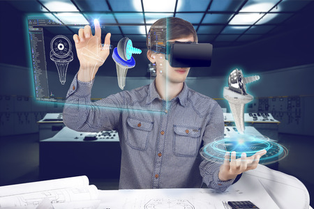 Futuristic medical scientist workplace. Male / man wearing shirt and vr glasses holding holographic prosthesis of knee and looking at virtual screen making medical analysis on futuristic plant background with control panels.