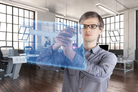 Virtual reality in engineering concept. Male  man wearing shirt and glasses making measurements of mechanical sketches on the virtual screen with ruler and pencil in the office Banco de Imagens