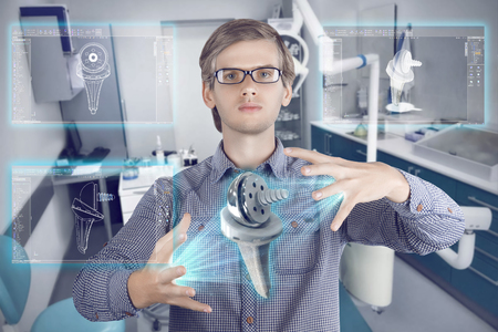 Futuristic medical scientist workplace. Male  man wearing shirt and glasses holding holographic prosthesis of knee and looking at virtual screens making medical analysis on futuristic plant background with control panels. Banco de Imagens