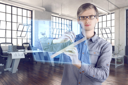 Virtual reality in engineering  architecture concept. Male  man architect wearing shirt and glasses making measurements of engineering  architectural sketches on the virtual screen with ruler and pencil in the office
