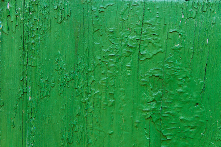 Wooden door texture with green paint is severely weathered and peeling