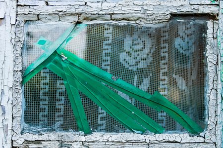 Background texture concept. Old cracked grungy window with green insulating tape and white curtains inside