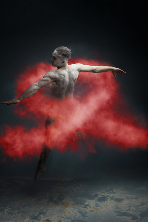Dancing in flour concept. Muscle fitness guy man male dancer in red dust  fog. Guy wearing white shorts making dance element in flour cloud on isolated grey background. HIV  AIDS red ribbon concept.