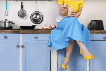 Retro pin up girl woman female housewife wearing colorful top, skirt and white apron holding cooked sweet strawberry milkshake sitting in the kitchen with utensils and tray with cupcakes. Stockfoto