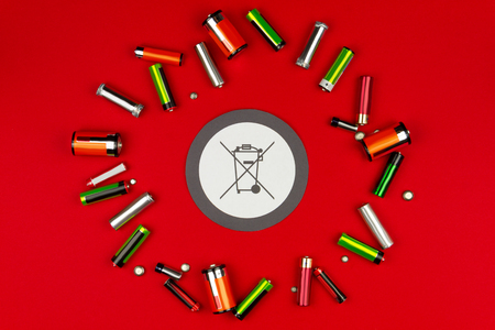 Colorful AA batteries isolated on red background. Renewable / green energy. Do not throw dead battery in garbage concept. Safe environment / ecology.