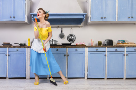 Retro / pin up girl woman female / housewife wearing colorful top, skirt and white apron holding mop singing and cleaning floor in the kitchen with blue cabinets and utensils. Housework concept 免版税图像